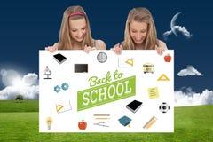 Imagen compuesta del cierre para arriba de dos mujeres jovenes que llevan a cabo a un tablero en blanco Imagen de archivo libre de regalías