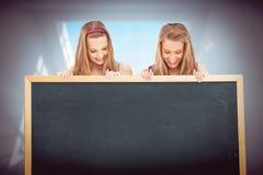 Imagen compuesta del cierre para arriba de dos mujeres jovenes que llevan a cabo a un tablero en blanco Imágenes de archivo libres de regalías