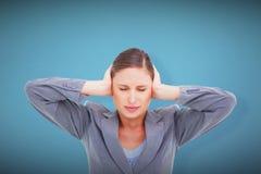 Imagen compuesta del cierre para arriba de la tendera enfadada que cubre sus oídos Imágenes de archivo libres de regalías