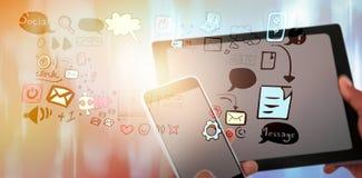 Imagen compuesta del cierre para arriba de manos usando la tableta digital y el teléfono móvil imagen de archivo libre de regalías