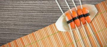 Imagen compuesta del cierre para arriba del sushi de color salmón con los palillos en placa Imagen de archivo