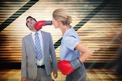 Imagen compuesta del colega de perforación de la empresaria con los guantes de boxeo Imágenes de archivo libres de regalías