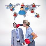 Imagen compuesta del colega de perforación de la empresaria con los guantes de boxeo Fotografía de archivo libre de regalías