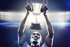 Imagen compuesta del deportista feliz que mira para arriba mientras que sostiene el trofeo Fotografía de archivo
