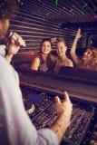 Imagen compuesta del disc jockey de sexo masculino que juega música con tres mujeres que bailan en la sala de baile Foto de archivo libre de regalías