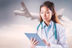 Imagen compuesta del doctor asiático que usa la tableta imagen de archivo libre de regalías