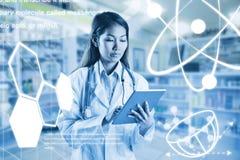Imagen compuesta del doctor asiático que usa la tableta Fotografía de archivo libre de regalías
