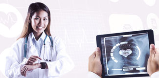 Imagen compuesta del doctor asiático que usa su reloj elegante Imagenes de archivo