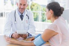 Imagen compuesta del doctor sonriente que toma el latido del corazón de un paciente imágenes de archivo libres de regalías