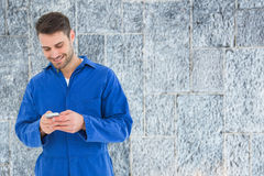 Imagen compuesta del envío de mensajes de texto masculino del mecánico a través del teléfono móvil Fotografía de archivo