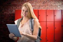 Imagen compuesta del estudiante feliz que usa la tableta Imágenes de archivo libres de regalías