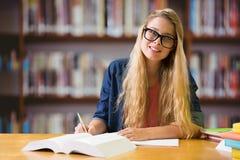 Imagen compuesta del estudiante que estudia en la biblioteca Imagen de archivo libre de regalías