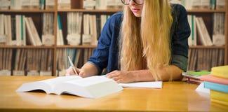 Imagen compuesta del estudiante que estudia en la biblioteca Fotografía de archivo libre de regalías