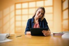 Imagen compuesta del estudiante que estudia en la biblioteca con la tableta Fotos de archivo libres de regalías