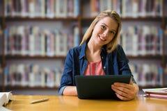 Imagen compuesta del estudiante que estudia en la biblioteca con la tableta Foto de archivo