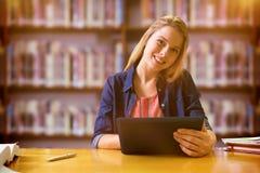 Imagen compuesta del estudiante que estudia en la biblioteca con la tableta Fotos de archivo