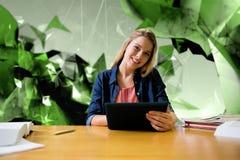 Imagen compuesta del estudiante que estudia en la biblioteca con la tableta Imagenes de archivo