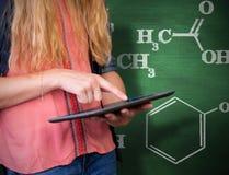 Imagen compuesta del estudiante que usa la tableta en biblioteca Imagen de archivo libre de regalías
