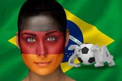 Imagen compuesta del fanático del fútbol alemán en pintura de la cara Fotografía de archivo libre de regalías