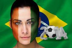 Imagen compuesta del fanático del fútbol de Costa de Marfil en pintura de la cara Fotografía de archivo libre de regalías