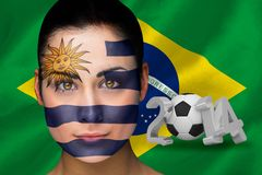 Imagen compuesta del fanático del fútbol de Uruguay en pintura de la cara Foto de archivo