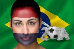 Imagen compuesta del fanático del fútbol holandés en pintura de la cara Imagen de archivo