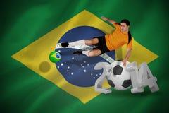 Imagen compuesta del futbolista en el salto anaranjado Foto de archivo libre de regalías