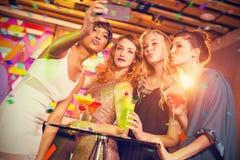 Imagen compuesta del grupo de amigos que toman el selfie del teléfono móvil mientras que teniendo cóctel Imagen de archivo libre de regalías