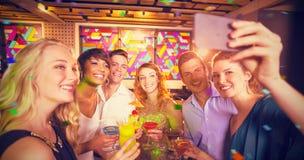 Imagen compuesta del grupo de amigos que toman el selfie del teléfono móvil mientras que teniendo cóctel Foto de archivo libre de regalías