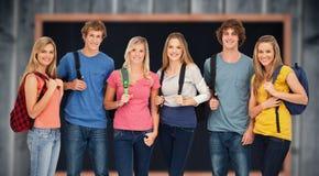 Imagen compuesta del grupo sonriente con las mochilas encendido como él sonríe Fotografía de archivo libre de regalías