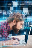 Imagen compuesta del hombre concentrado que trabaja en el ordenador portátil Fotografía de archivo