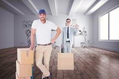 Imagen compuesta del hombre de entrega feliz que se inclina en la carretilla de cajas Imágenes de archivo libres de regalías