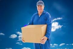 Imagen compuesta del hombre de entrega feliz que sostiene la caja de cartón Foto de archivo libre de regalías