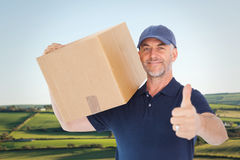 Imagen compuesta del hombre de entrega feliz que sostiene la caja de cartón que muestra los pulgares para arriba Imagenes de archivo
