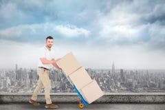 Imagen compuesta del hombre de entrega que empuja la carretilla de cajas Foto de archivo