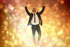 Imagen compuesta del hombre de negocios alegre con los brazos para arriba que anima Fotografía de archivo