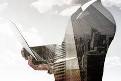 Imagen compuesta del hombre de negocios con el reloj usando la PC de la tableta Imagen de archivo