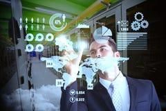 Imagen compuesta del hombre de negocios concentrado que mide algo con sus fingeres Fotografía de archivo