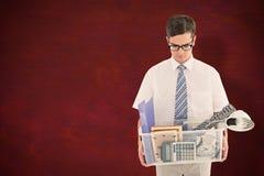 Imagen compuesta del hombre de negocios encendido que sostiene la caja de pertenencia foto de archivo