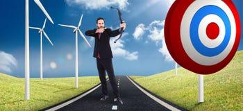 Imagen compuesta del hombre de negocios enfocado que tira un arco y una flecha Imagen de archivo