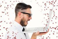 Imagen compuesta del hombre de negocios frustrado geeky que mira su ordenador portátil Fotos de archivo libres de regalías