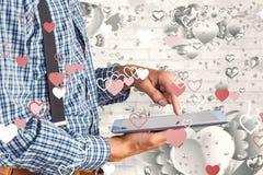 Imagen compuesta del hombre de negocios geeky usando su PC de la tableta Fotos de archivo libres de regalías