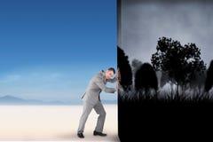 Imagen compuesta del hombre de negocios que empuja lejos escena Imágenes de archivo libres de regalías