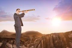 Imagen compuesta del hombre de negocios que mira a través del telescopio Imágenes de archivo libres de regalías