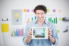 Imagen compuesta del hombre de negocios que muestra la tableta digital con la pantalla en blanco en oficina creativa Fotografía de archivo libre de regalías