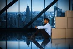 Imagen compuesta del hombre de negocios que se inclina en las cajas de cartón contra el fondo blanco imagen de archivo libre de regalías