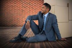 Imagen compuesta del hombre de negocios que se sienta cerca de las cajas de cartón contra el fondo blanco foto de archivo