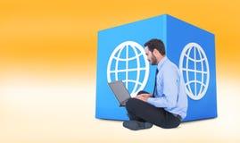 Imagen compuesta del hombre de negocios que se sienta en el piso usando su ordenador portátil Fotografía de archivo libre de regalías