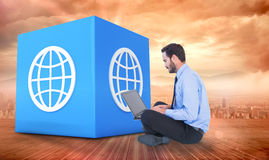 Imagen compuesta del hombre de negocios que se sienta en el piso usando su ordenador portátil Foto de archivo libre de regalías