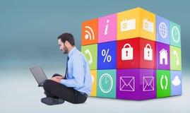 Imagen compuesta del hombre de negocios que se sienta en el piso usando su ordenador portátil Imagen de archivo